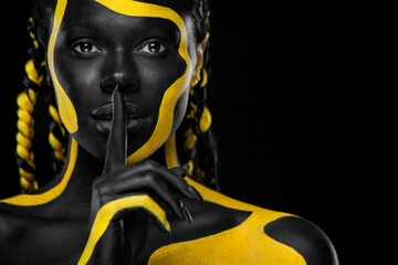 Obraz Face art. Girl showing gesture quietly, asks remain silent with finger. Woman with black and yellow body paint. Young african girl with colorful bodypaint. An amazing afro american model with makeup. - fototapety do salonu