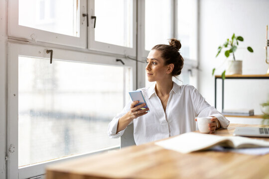 Creative business woman using smartphone in loft office