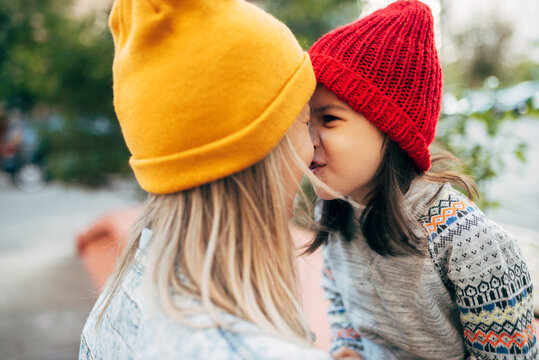 Candid portrait of a playful little girl in red hat hugging her mom in yellow hat. Cute kid embracing her mother enjoying the time together outside. Mother and daughter share love. Mother's day.