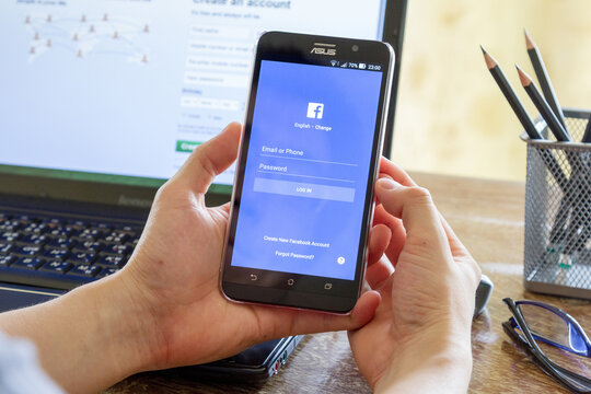 CHIANG MAI, THAILAND - MAY 24, 2016: man hand holding Asus Zenfone 2 mobile phone with screen shot of Facebook application