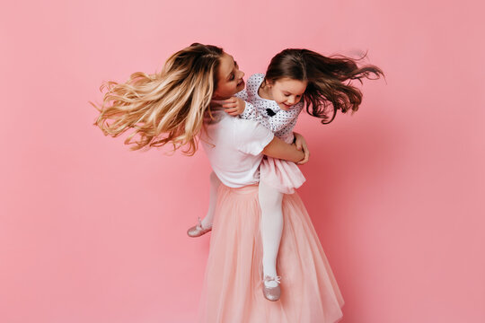Blonde woman holds daughter in her arms and spins on pink background. Snapshot of curly mom and child in bright romantic dresses