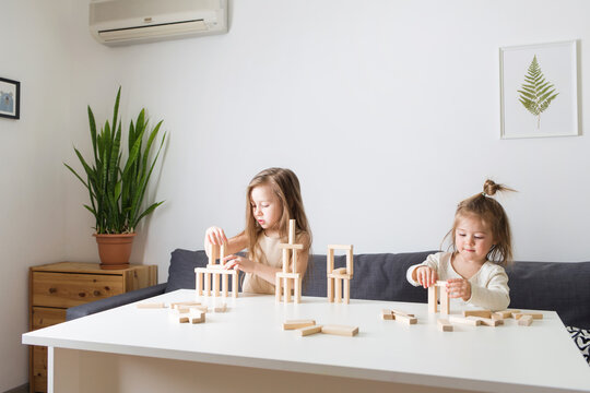 kids playing with wooden jenga constructor. girls build towers from toy rectangular blocks. concept of developing fine motor skills, games. Leisure activities for children at home