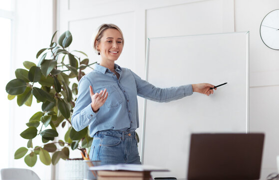 Online education. Young female tutor pointing at empty blackboard with space for design, giving web lesson from home