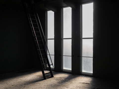 Metal ladders silhouette against tall bright glass windows going up into roof of room in dark old building shadows on the floor giving a creepy eerie atmosphere with no people there