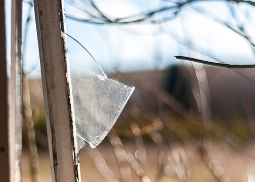Broken glass following burglary in open window with metal frame sharp edge shard of glass sticking out in derelict building after vandalism