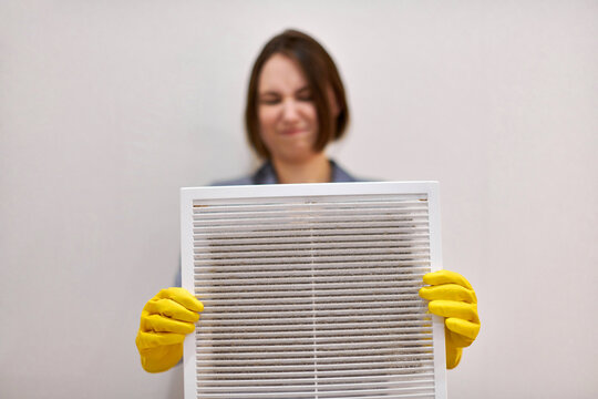 Woman holding dirty and dusty ventilation grille, disgusted