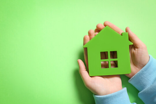 Woman holding house model on light green background, top view. Space for text