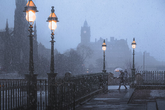 A winter storm of snow flurries in Edinburgh, Scotland disrupts a commuter with an umbrella in front of the Walter Scott Monument and Waverley Station.