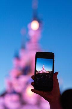 A person photographs the Disney Princess Castle. August 28, 2019, Paris, France.