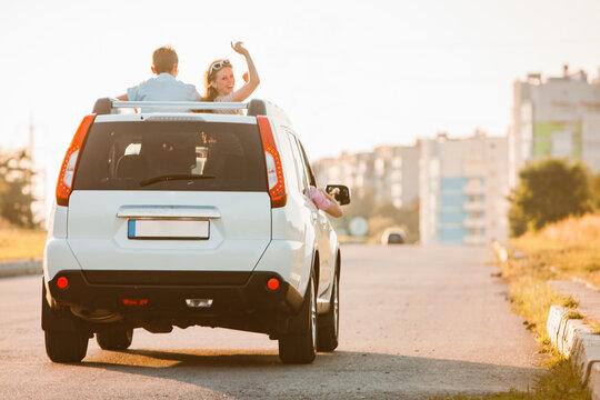 car travel. fun happy people stick put of sun roof