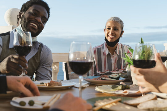 Young multiracial friends doing appetizer and drinking red wine on house patio during sunset time