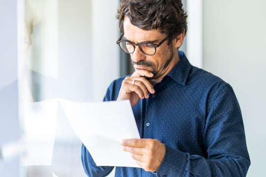 Business man wearing glasses  holding paper document. Successful male portrait thinking and reading contract at the office by the window