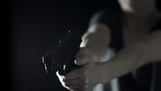 A Woman's hands holding a .45 caliber handgun. Female training and concealed carry concept