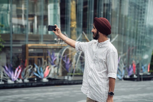 Smiling man with turban standing in front of shopping mall and taking selfie with mobile phone