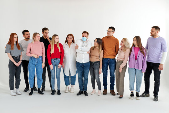 sick male feels constrained and uncomfortable among healthy people, afraid of infecting someone, group of people look at him, isolated over white background