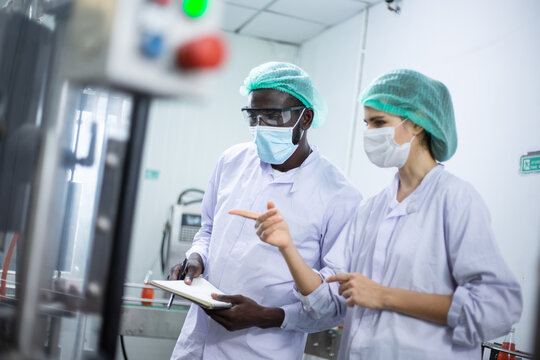 African American black man and woman worker inspecting drink product on bottling factory machinery. Process of beverage industrial concept. diversity people working together
