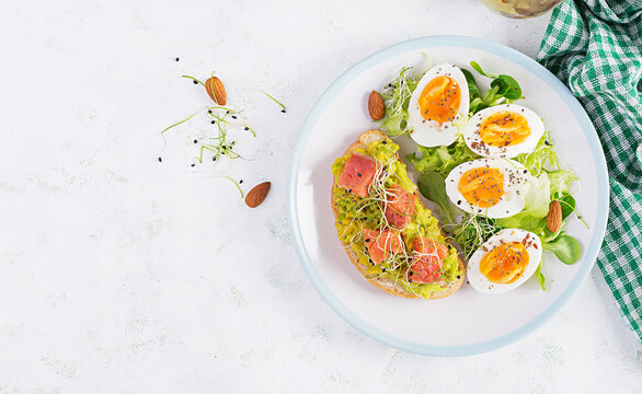 Breakfast. Healthy open sandwich on  toast with avocado and salmon, boiled eggs, herbs, chia seeds on white plate  with copy space. Healthy protein food. Top view, overhead