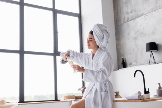 Woman in towel and bathrobe pouring champagne in bathroom