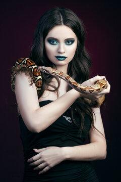 girl brunette green make up eyes gaze close up portrait with a snake yellow brown mottled python on a black pink background