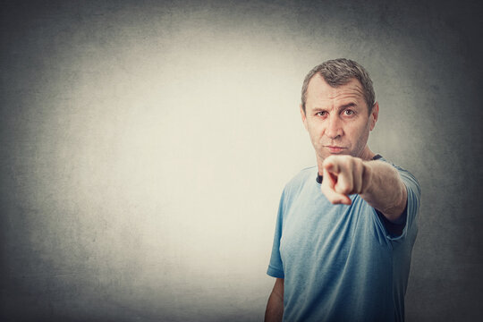 Confident and determined middle age man pointing index finger to camera, like blaming or accuse someone, isolated on grey wall background with copy space. Senior male showing with forefinger to you