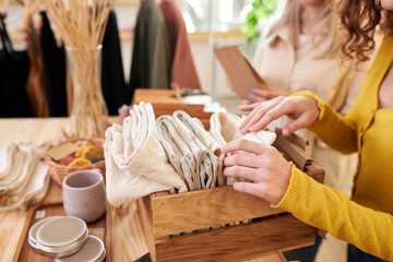cropped female customers examining stack of organic clothing and cotton colors in eco-friendly shop...