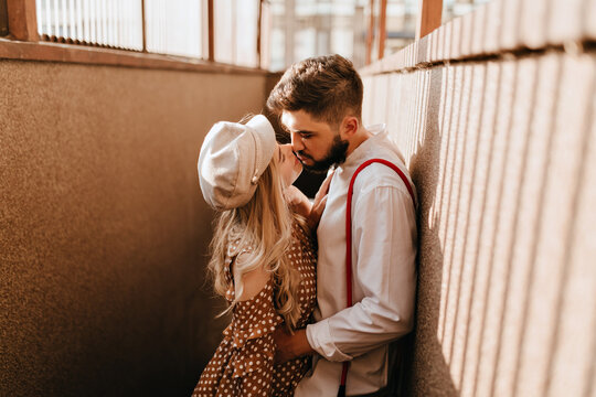 Man embraces his blonde girlfriend in beige cap. Romantic couple enjoying sunny day and kissing