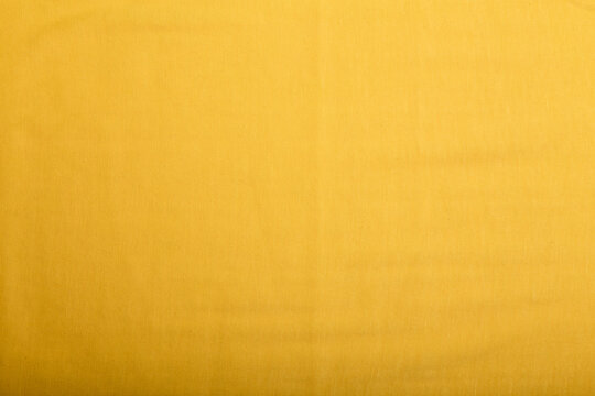 Texture of yellow cotton straight fabric, background or backdrop. Clothing, sewing, gressmaking, haberdashery. Copy space.