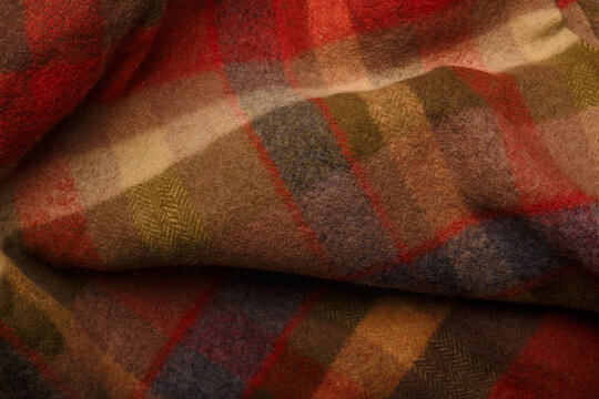 Texture of checkered plaid of warm autumn colors, wrinkled woolen fabric for cozy leisure at home or outdoors. Background or backdrop.