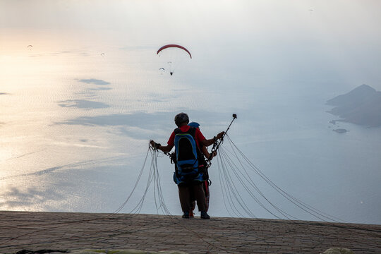 Fethiye Ölüdeniz Babadağ is considered one of the most important paragliding regions in the world. Muğla, Turkey. Group of brave paragliders take off from mount Babadag near the resort of Oludeniz.