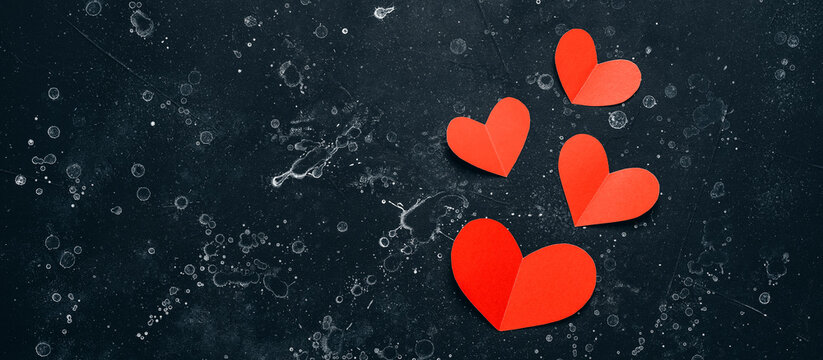 Banner of red paper hearts on black stone grunge background. Valentine's Day. Top view, flat lay.