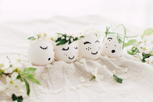 Natural easter eggs with drawn cute faces in floral wreaths on linen fabric with bloom in light