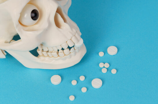 On a blue background, a skull that holds pills in its mouth. Pills are scattered nearby