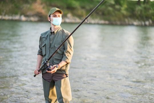 Masked fisherman fishing, covid coronavirus and air pollution concept