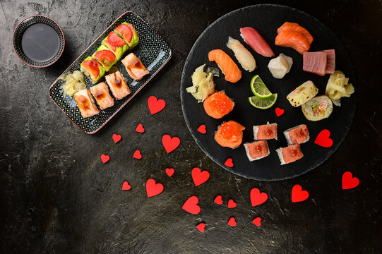 Set of different kinds of sushi rolls with salmon avocado and shrimp. Delicious Japanese dishes. Romantic dinner concept. All you can eat sushi. Uramaki with hearts design