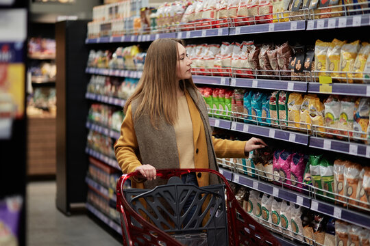 A woman walks through a supermarket with a shopping cart and selects goods. Shelves with a large number of products.