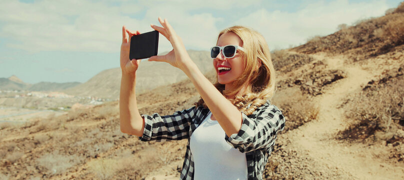 Portrait of happy young woman taking selfie picture by smartphone on a hiking trail on top of the mountain, Tenerife, Canary Islands, Spain