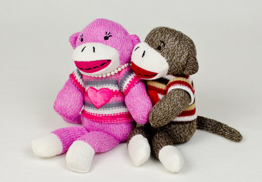 A pair of sock monkeys holding eachother
