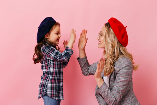 Curly stylish mom and daughter play patty-cake on pink background. Portrait of blonde woman and child in fashionable french berets