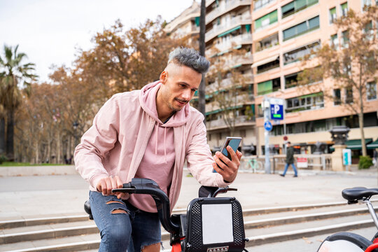 Stylish mid adult man renting bicycle with mobile phone in city