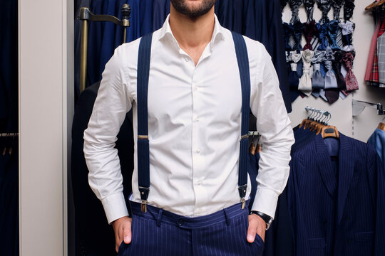 Customer in white shirt and blue suspendersin tailors boutique