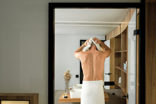 Mature man wearing towel drying hair in bathroom after shower at home