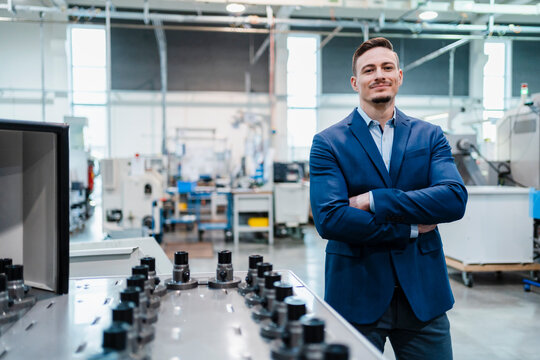 Smiling businessman with arms crossed by manufacturing equipment in factory