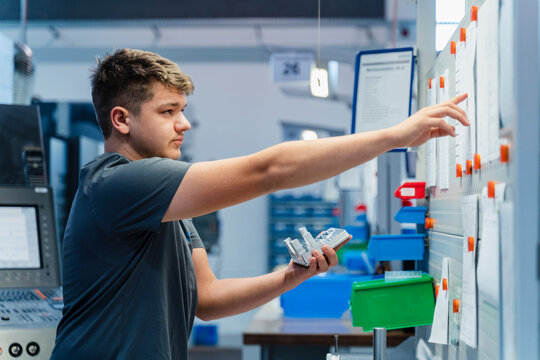Young engineer reading paper on whiteboard while standing at industry