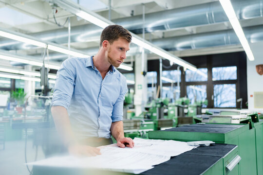 Male professional with blueprint looking away in factory