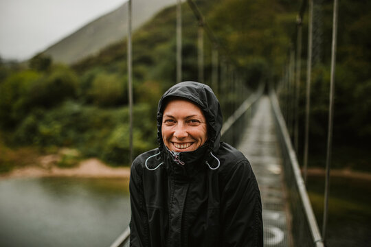 Smiling woman standing on suspension bridge over Sella river on rainy day