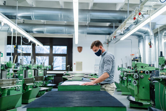 Businessman with digital tablet examining blueprint in factory during pandemic