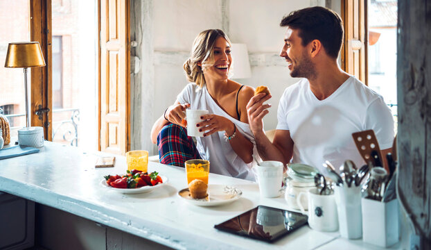 Happy young couple sitting at table and having breakfast at home