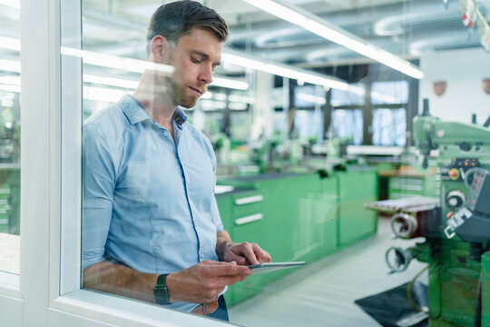 Mid adult businessman working on digital tablet seen through glass in industry
