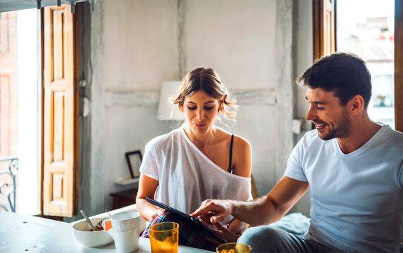 Cheerful couple eating breakfast