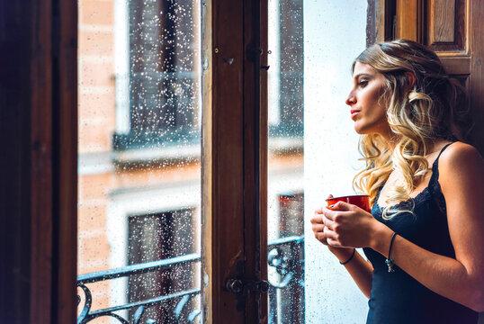 Beautiful female watching out of window